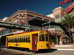 A trolley car passes beneath the pedestrian bridge leading to Centro Ybor in Ybor City Historic District